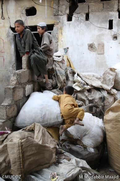 A child climbs up a pile of recyclable paper